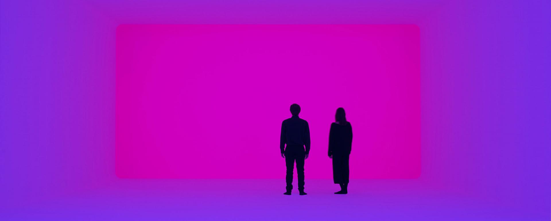 Zwei Menschen stehen in einem Raum aus blauem und violettem Licht