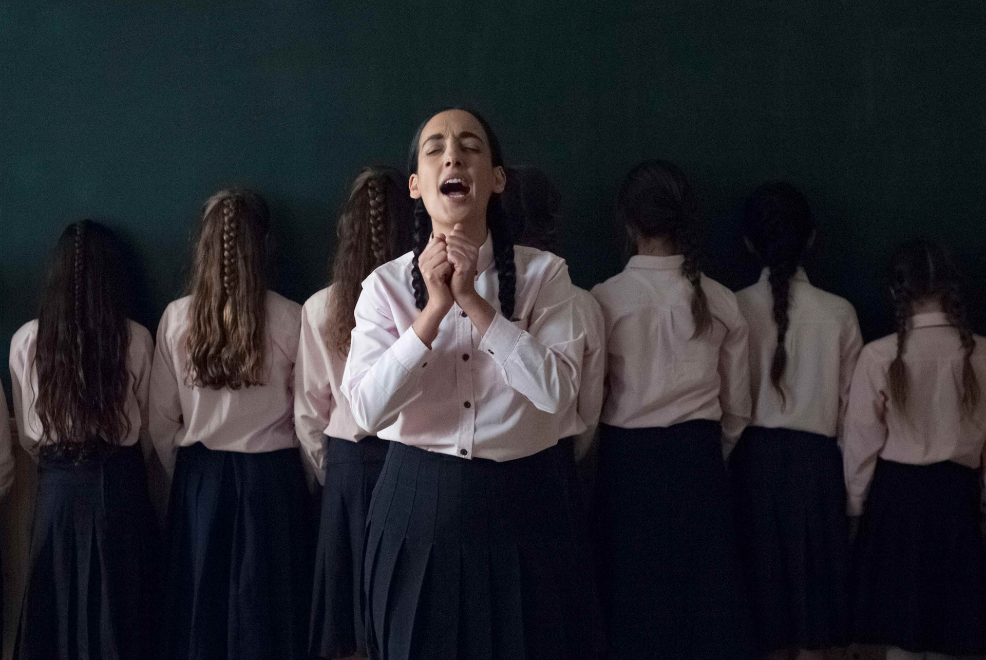 A group of girls in the clothes of Orthodox Jewish schoolgirls stands facing the wall in front of a blackboard. Victoria Hanna stands in front of it in the middle, singing with her eyes closed and her hands in front of her chest.