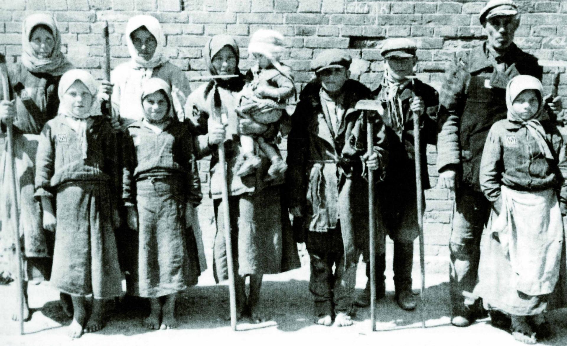 Zehn Personen, überwiegend unbeschuht und größtenteils Kinder, mit Ackergeräten