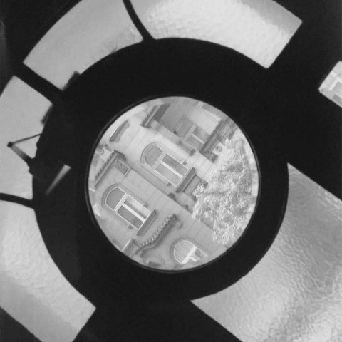 Black-and-white photograph: View of the buildings opposite through a transom window
