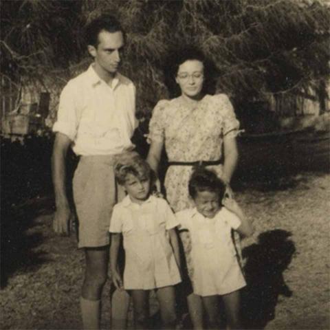 Die Aufnahme zeigt einen Mann, eine Frau, vor ihnen zwei Kinder, alle stehen im Freien. Die beiden Jungs und der Mann tragen kurze Hosen, die Frau ein kurzärmeliges Kleid mit floralem Muster.