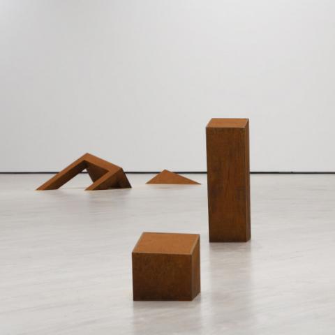 In einem leeren Raum verteilte Objekte aus gerostetem Eisen, sie wirken teilweise wie eingesunken