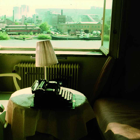 Vor dem geöffneten Fenster sieht man eine Schreibmaschine auf einem kleinen Tisch und eine Lampe mit schiefsitzendem Schirm