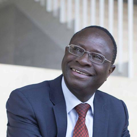 Karamba Diaby sitzt auf einer Treppe, er trägt einen blauen Anzug mit rotkarierter Krawatte