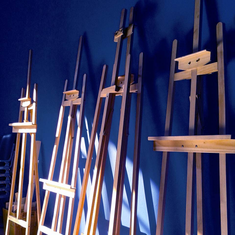 Several easels in front of a dark blue wall