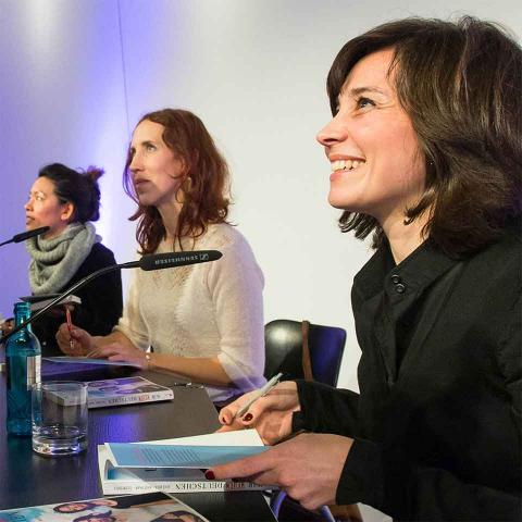 Drei Frauen im Profil an einem Tisch, die lächelnd Bücher signieren
