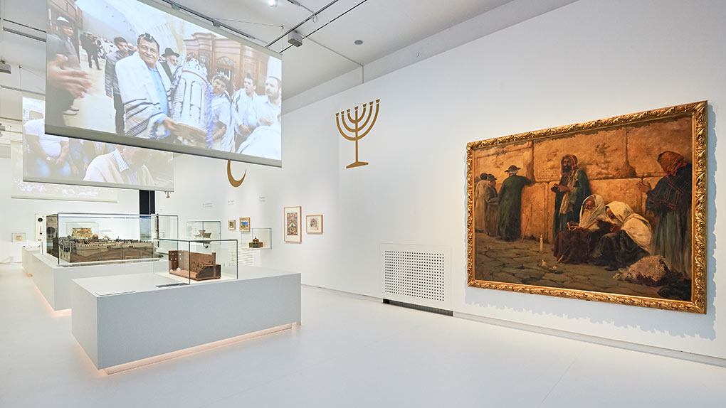 The central room of the exhibition Welcome to Jerusalem contains models of famous buildings, video projections and a big oil painting.